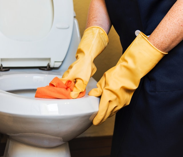 person cleaning toilet with rubber gloves on