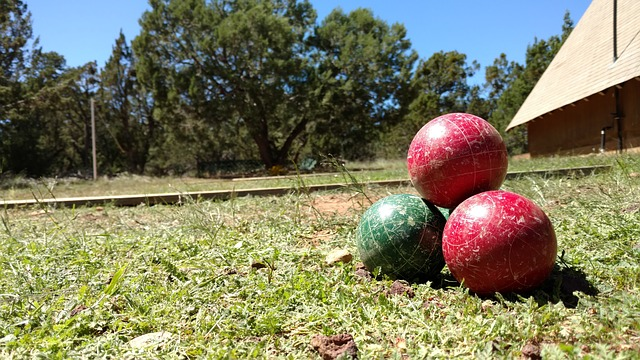 four stacked bocce balls on green grass