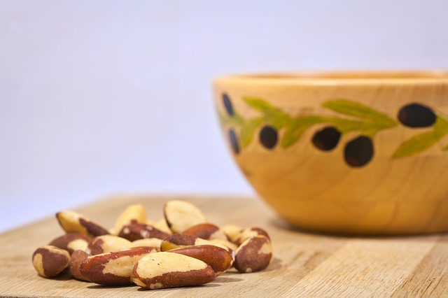 selenium containing brazil nuts in front of wooden bowl
