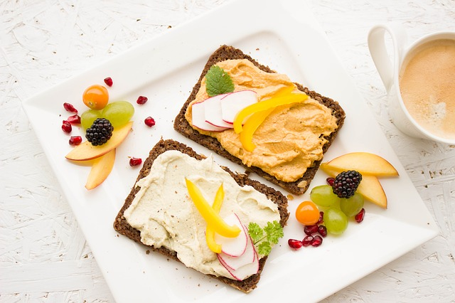 nutritious breakfast hummus on toast with fruits and vegetables next to coffee