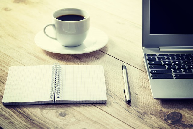 notebook and pen next to computer and cup of coffee