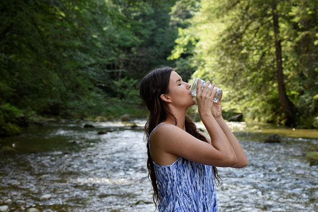 detox by drinking water woman drinking water from glass in nature
