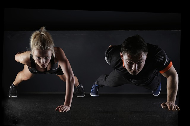 man and woman doing one handed pushups