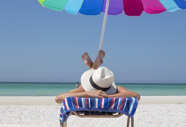 person laying on beach under umbrella soaking up vitamin d